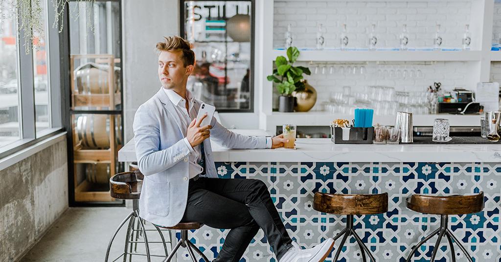 Man drinking beverage using iphone