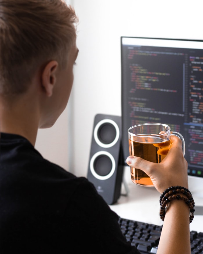 Developer writing code and drinking tea