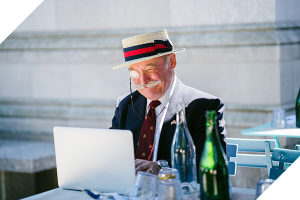 Gentleman wearing a straw hat and a monocle using a laptop