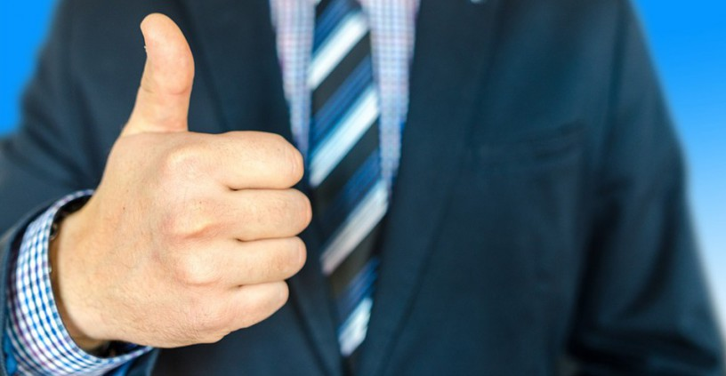 Man with suit and tie giving thumbs up
